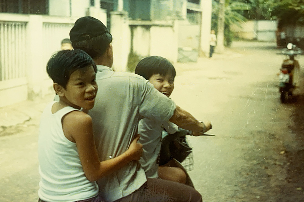 Two boys holding onto their father during a bike ride down a street in Viet Nam
