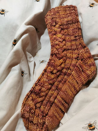 A hand knitted BFL DK sock with cables made from 100% British Yarn, hand dyed by purrmaid yarns
