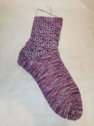 """A hand knitted burgundy sock. The hand dyed yarn is """"reverie"""" from Indie Dyer Purrmaid Yarns"""