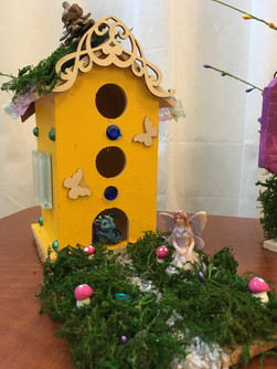 The tiny fairy gardens quietly beside her bright yellow home.