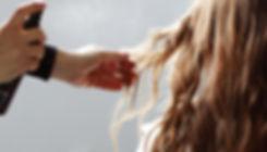 person spraying woman's hair