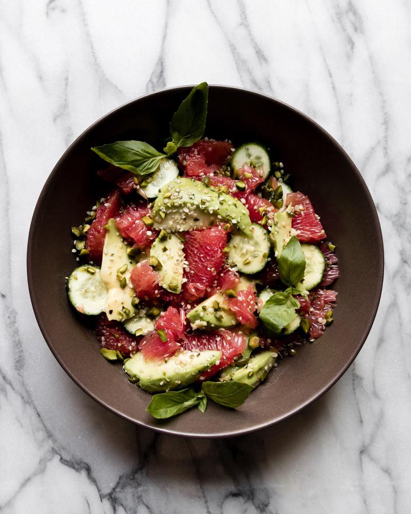 Grapefruit Avocado Cucumber Basil Pistachio Salad on Marble table brown bowl