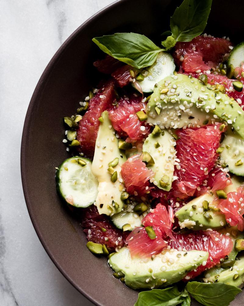 Grapefruit Avocado Salad Cucumber Basil Pistachio on marble table brown plate