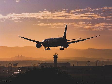 white-passenger-plane-flying-over-the-ci