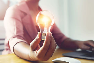 hand-holding-light-bulb-with-using-laptop-office-concept-saving-energy-power_34152-1907.jp