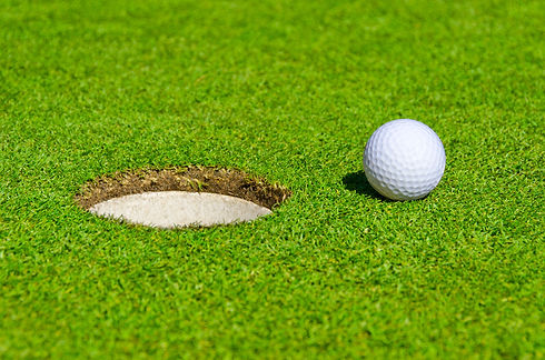 A hole over golf ball on green. Shallow
