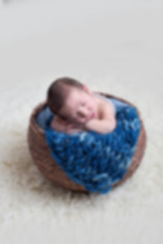 newborn baby boy posed in basket during newborn photo shoot in Concord MA