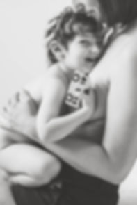naked toddler being cuddled by mom in black & white photography session in studio Concord MA
