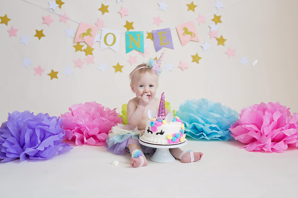 unicorn themed cake smash with rainbow outfit and headband frosting everywhere