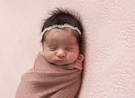 newborn baby posed on blanket with pearl headband in-studio newborn photography