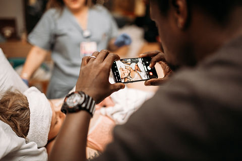 dad helping mom during labor birth photographer