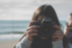 primer plano de una chica tomando fotos con una camara reflex