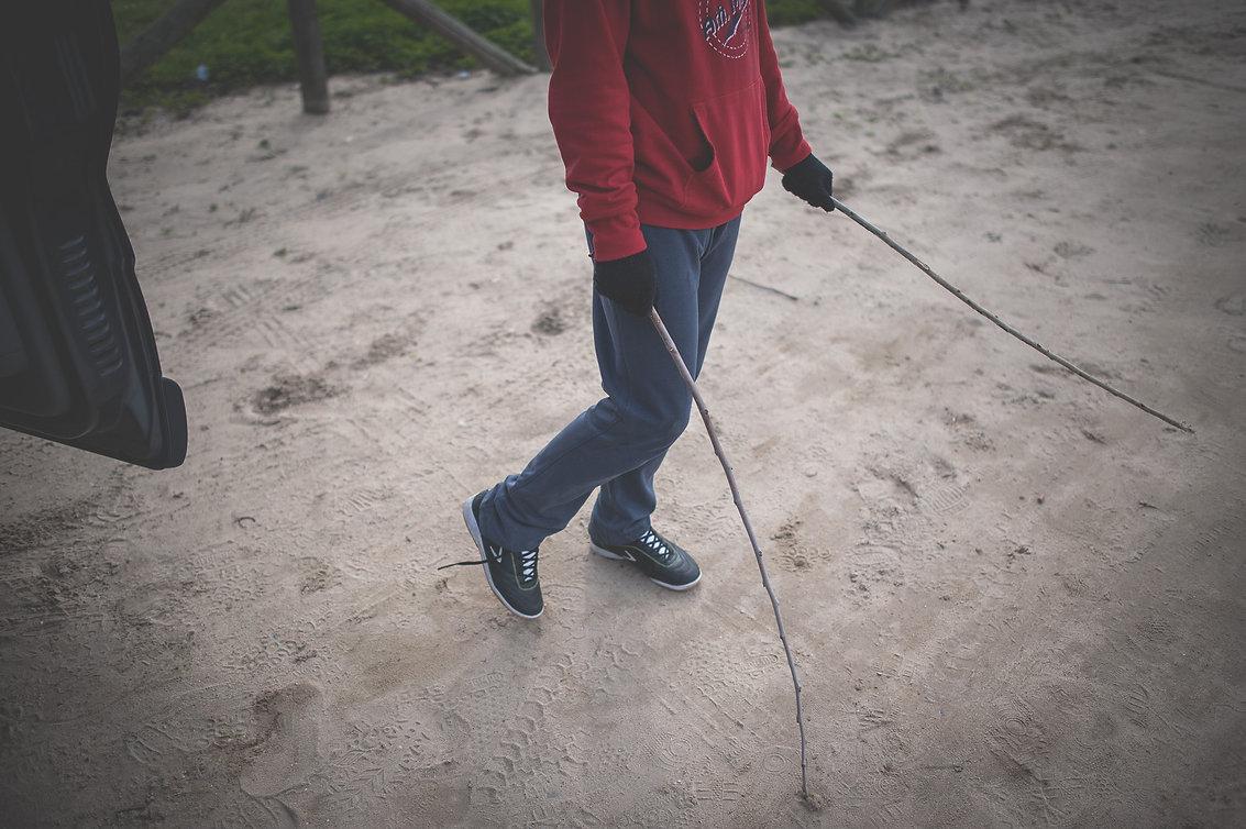 chico en la playa con dos palos