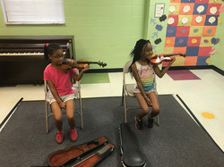 girls playing violin at camp