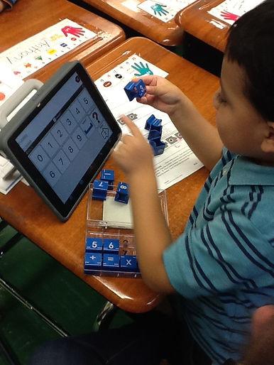 Young student using iPad and math manipulatives