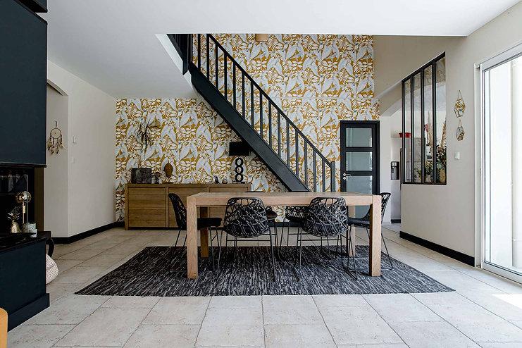 salle a manger donnant sur l'escalier principal bois repeint en noir et papier peint moutarde et blanc motif vegetal table bois et chaises tressees grises meuble sous escalier verriere atelier et porte vitree gris metal agence dekode deco interieure nantes