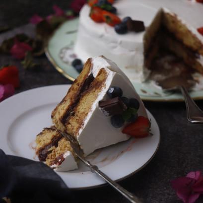 Torta con crema al cioccolato, panna e frutti rossi