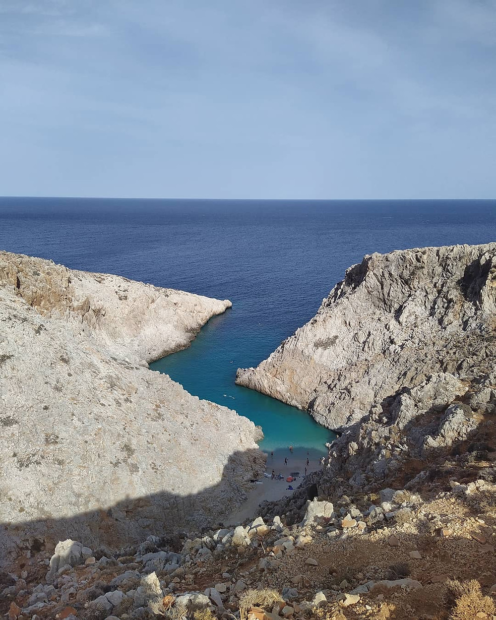 Picture of Seitan Limania beach, Akrotiri, Chania, west Crete, from above. The beach is in a narrow inlet S-type formed, with limestone rocky landscape and turquoise water. Photo taken on afternoon of October 2020, from the West viewing to the beach