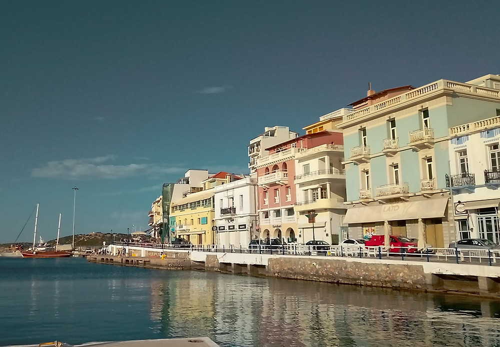 Part of the coastal walkway in Agios Nikolaos, Crete, in the area of the old port, near the lake. As part of the promenade, picturesque, colorful, buildings of the coastal road are also depicted.