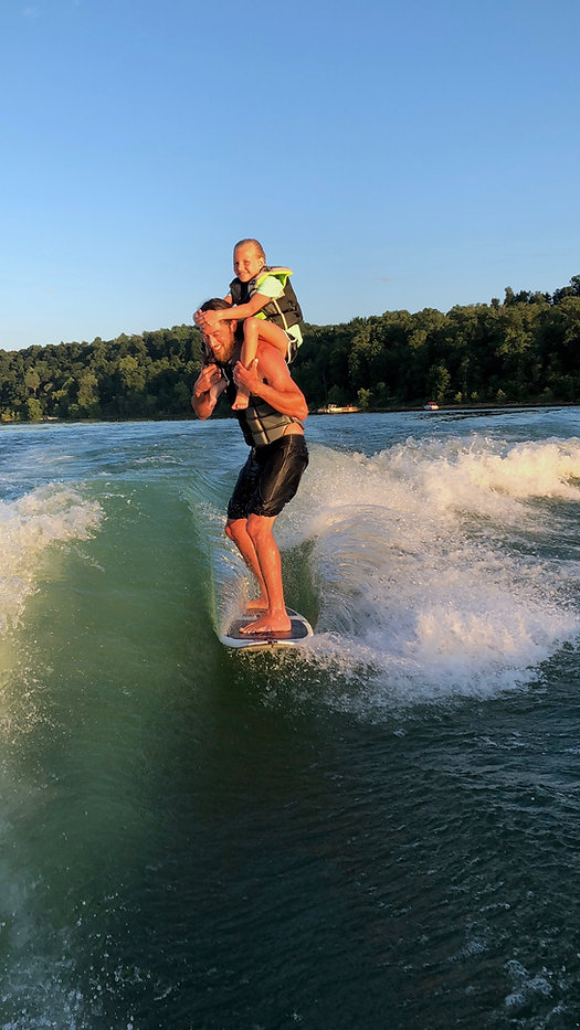 Wakesurf Orlando head coach Captain Tarzan taking Abby for a sunset wakesurfing session on the Phase 5 Swell wakesurf board