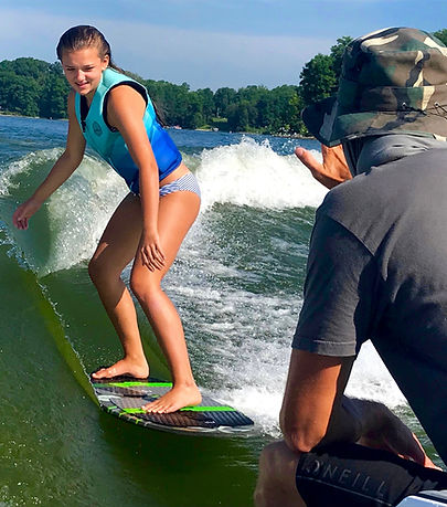 Wakesurf Orlando head coach Captain Tarzan teaching Elle wakesurfing lessons on the Phase 5 Matrix wakesurf board