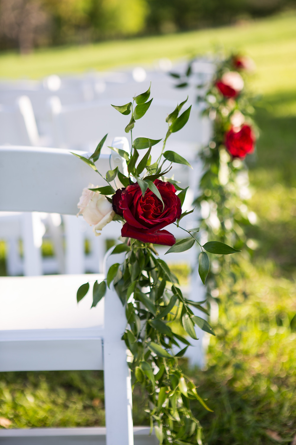 Floral aisle marker with greenery and roses