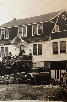 A sepia-toned photograph of a Dutch-Colonial-style house with a 1920's car parked in front of it. A stone wall wraps around the front of the house. Two figures lounges on the stone front porch.