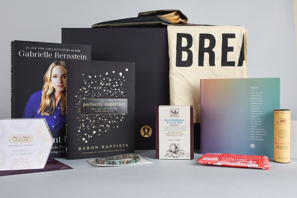 Lululemon gift box image with Gabrielle Bernstein book, Baron Baptiste book, Soapbox Soaps, Numi Tea, Lululemon gift card and other small items.