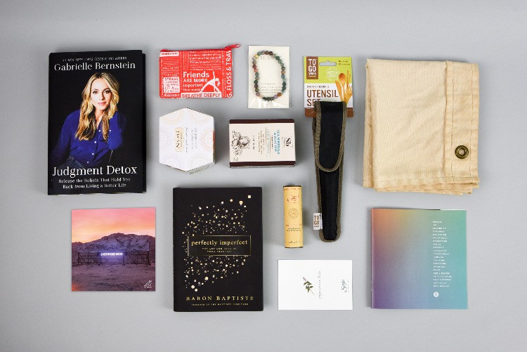 Flat-lay photo of 12 items included in the Lululemon Influencer box: 2 books, a box of tea, a bar of soap, a gift card, a flag, two printed papers, and 3 other small, unidentified items.