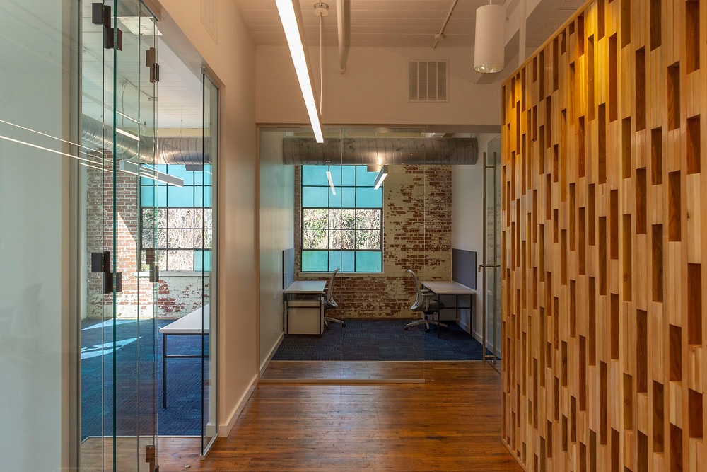 The exposed brick of an office is visible through a modern glass sliding door.