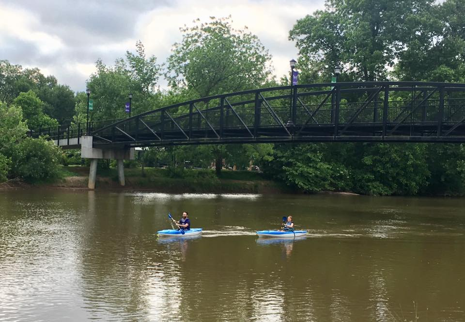 Two people kayak under Cramerton's iconic Goat Island Bridge