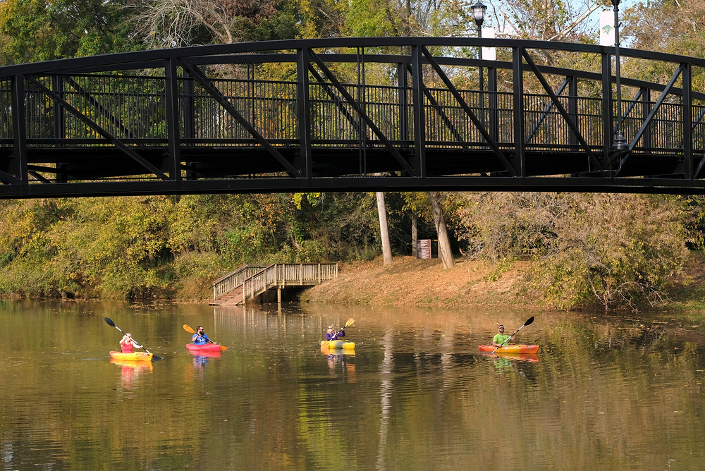 Three Paddlers float on the South Fork River under the Goat Island Bridge