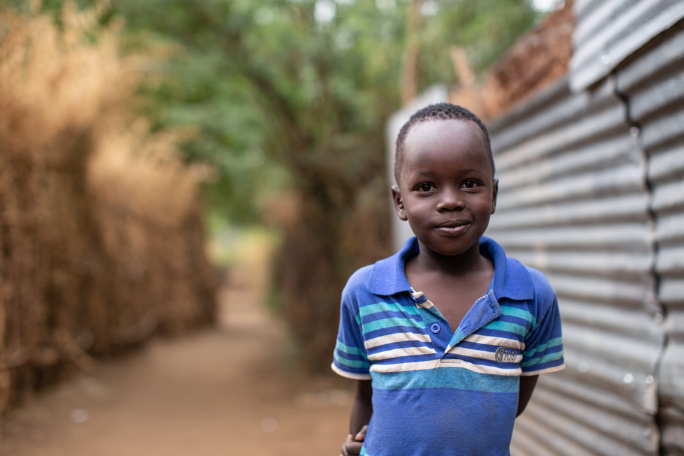 Akech, a Sudanese refugee, poses in the dusty alleyways of the Kakuma refugee camp.