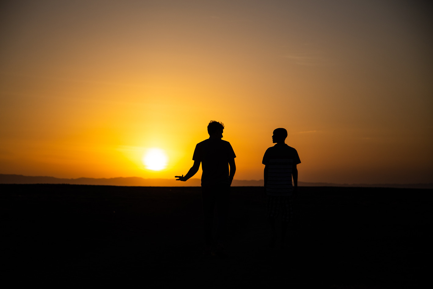 The sun sets over two men walking the shores of Lake Turkana in northern Kenya.