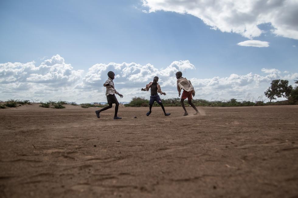 Boys play football on a dirt pitch on the outskirts of Kakuma refugee camp.