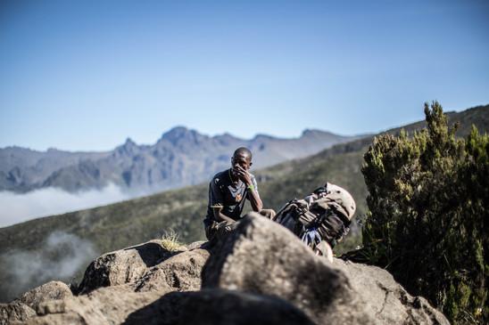 A Kilimanjaro porter takes a smoke break near the Machame camp, with the Shira plateau behind him.