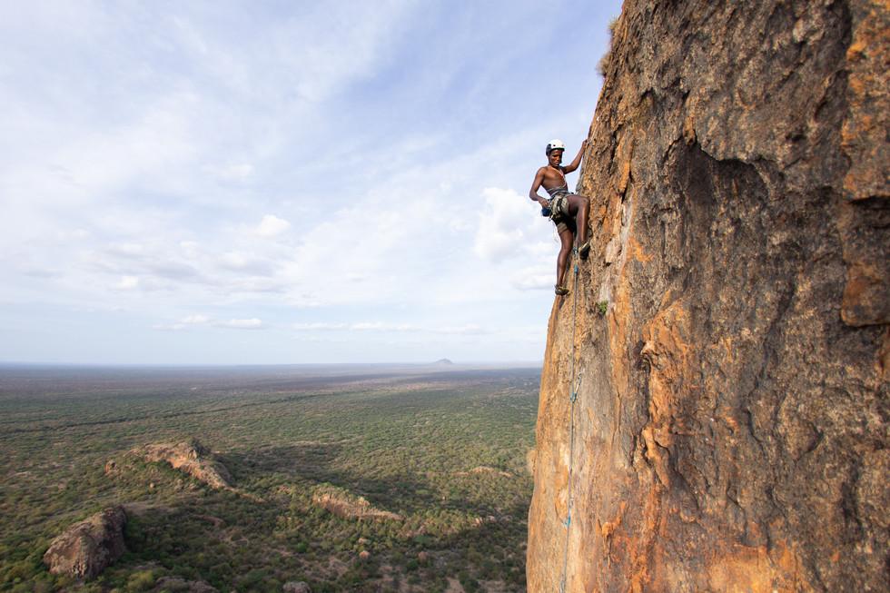 Ian Lekiluai, a Samburu moran, leads his way up the delicate flakes of The Mouse near Ololokwe. For Climbing Magazine.