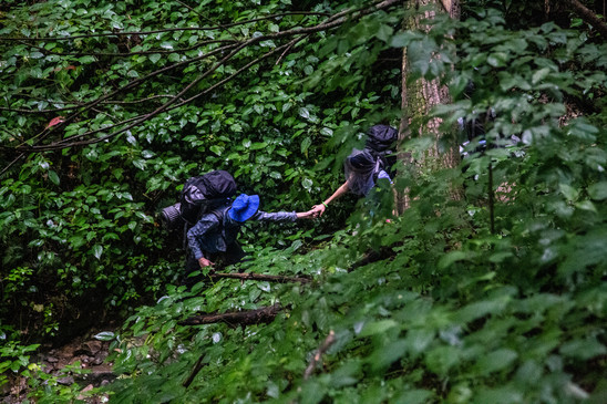 A student helps his crewmate down a steep trail in Pisgah National Forest on an expedition with the North Carolina Outward Bound School.