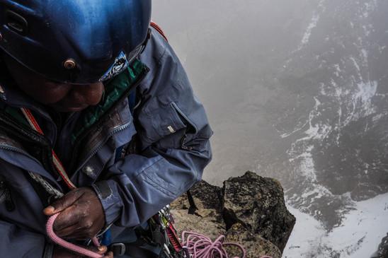 David Muigai piles rope at a belay on Shipton's Notch, 17,000 feet abover sea level on Mount Kenya. Published in Alpinist Magazine.