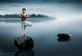 Dawn yoga, tree pose on a rock in a misty lake