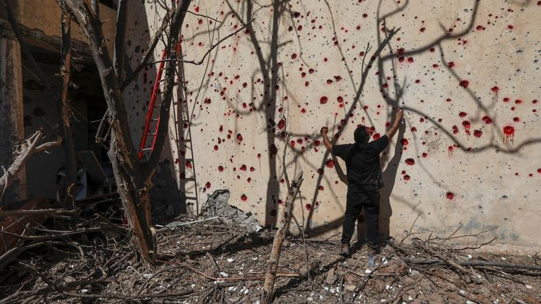 A member of KDPI sprays red paint at holes in a wall made by shrapnel from a rocket attack in Arbil on September 12, 2018. (AFP)
