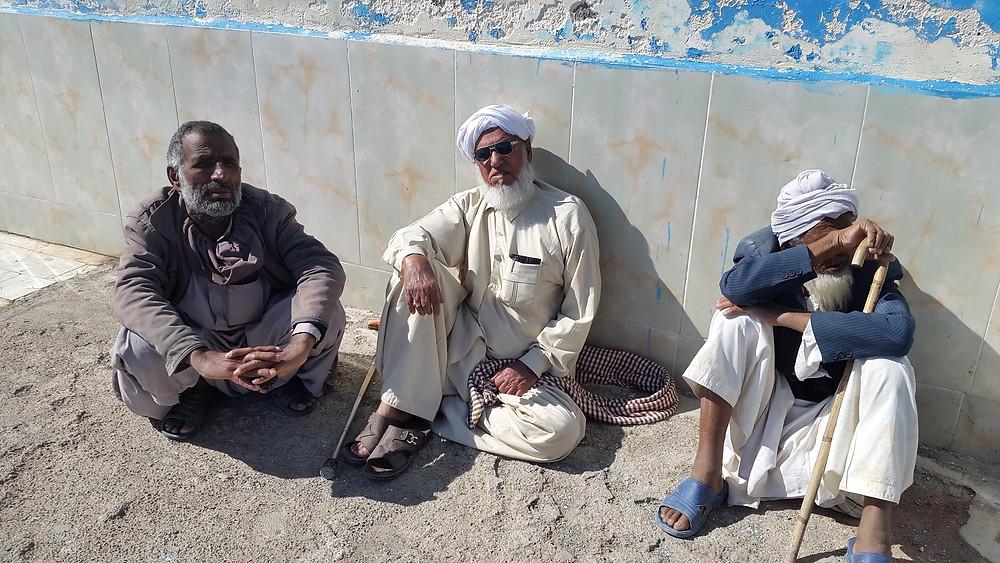 Pakistan it looks… Baloch elders reclining along a street.