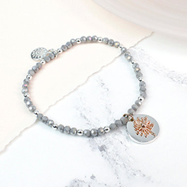 Pom grey bead bracelet with a rose gold dandelion clock charm