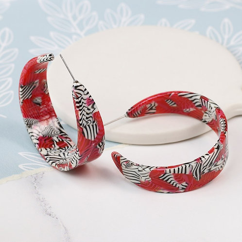 Pom red acrylic earrings with striking zebra pattern