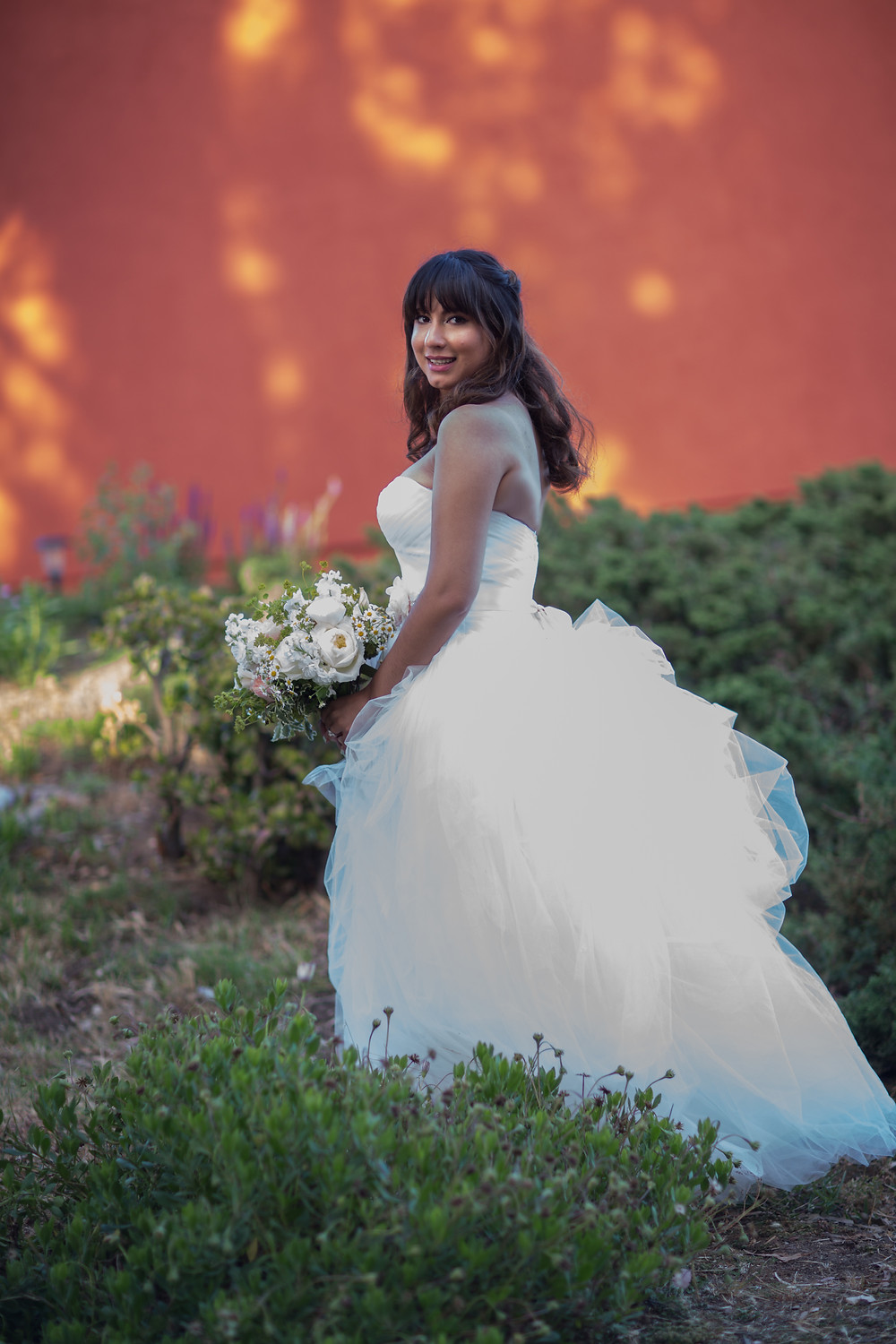 The light filtering through the trees onto the orange wall created a perfect happy background to this happy bride.
