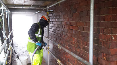 Man pressure washing brickwork