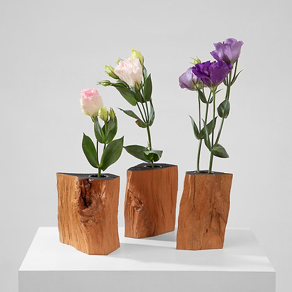 Three unique, whimsical, asymmetrical vases made from thick pieces of cherry wood each with a flower inside