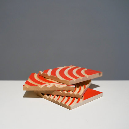 A stack of four maple wood coasters engraved with decorative concentric circles and a red face