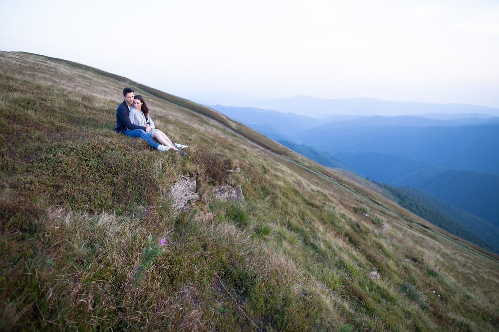 Couple sitting on field at edge of cliff