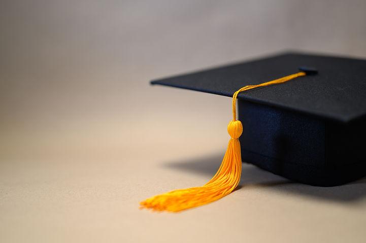 black-graduation-hat-placed-brown-paper.